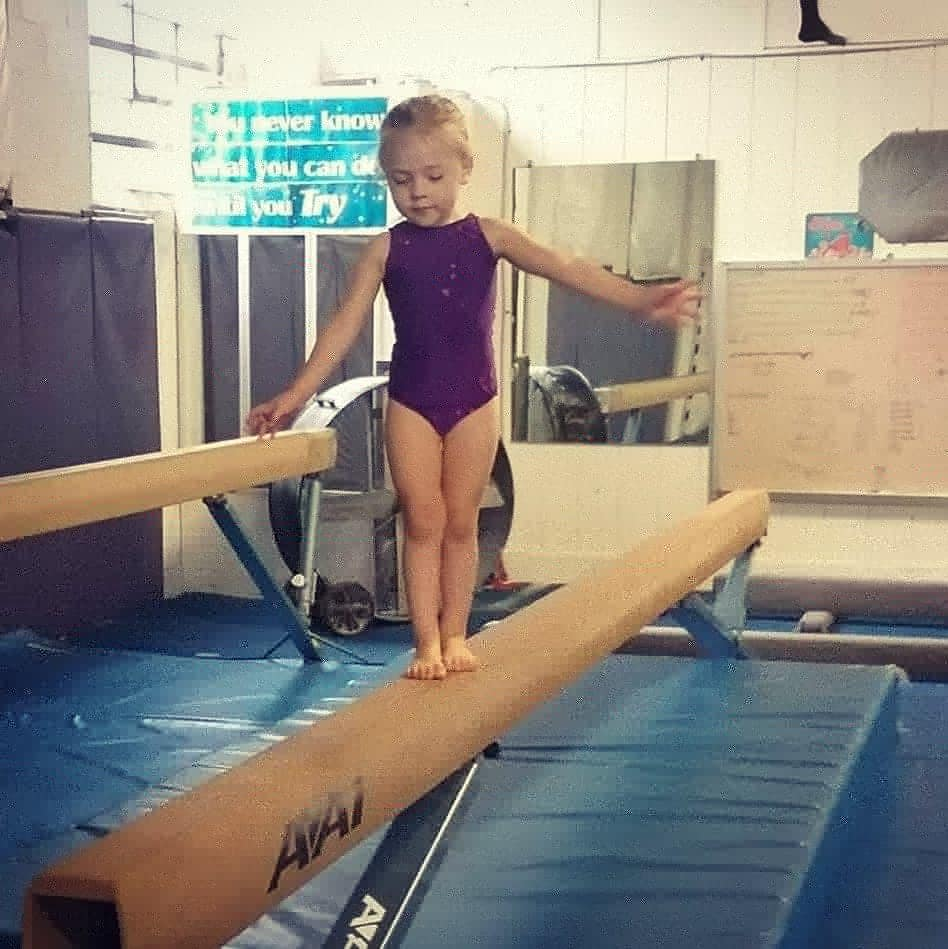 young girl with blonde hair in a purple outfit balancing on a beam